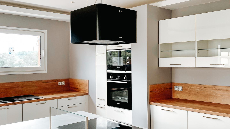 cuisine avec un grand plan de travail intégrant plaque de cuisson et hotte décorative suspendue